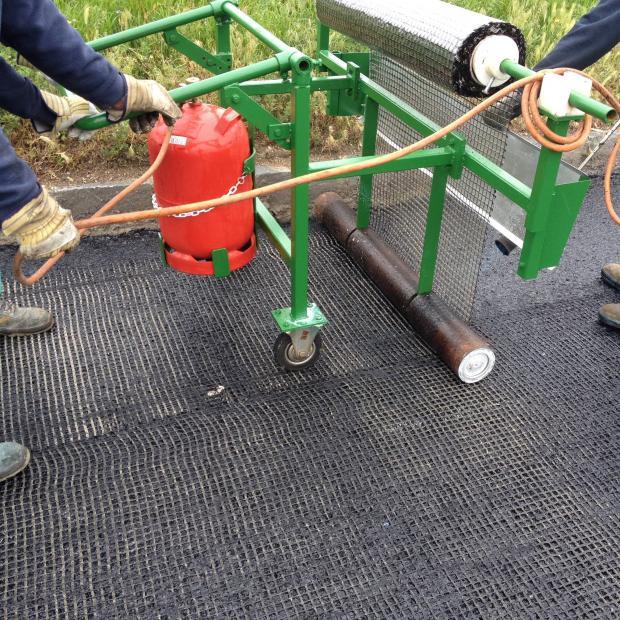 Ręczne rozkładanie siatek S&P do wzmocnień nawierzchni asfaltowych